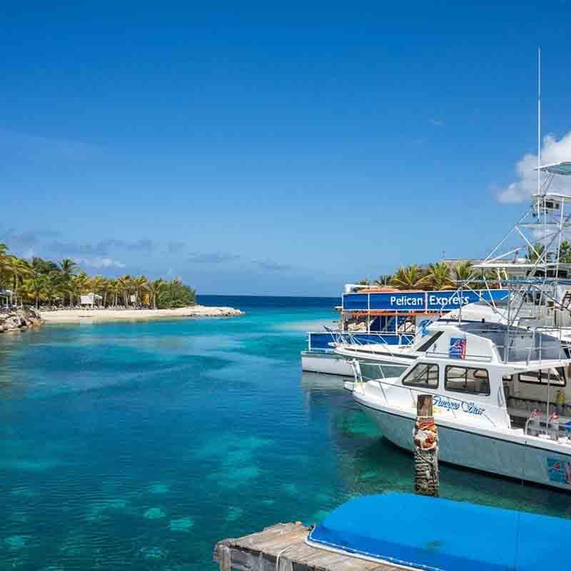 Lagune met boten in een helder blauwe zee in Curacao - aanbiedingen Vriendenprijsreizen