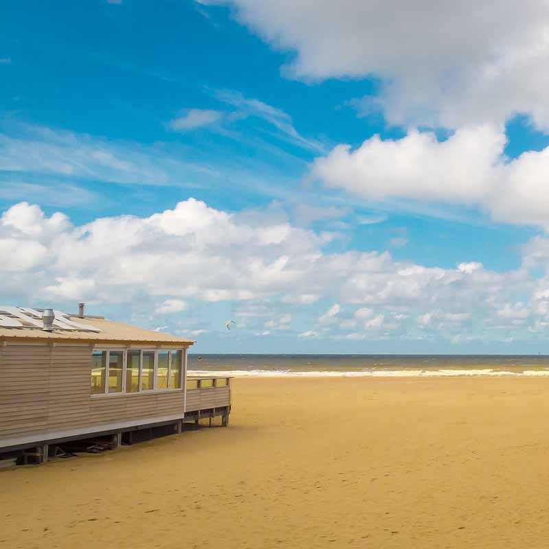 Strandhuis op het strand met de zee op de achtergrond - Vriendenprijsreizen