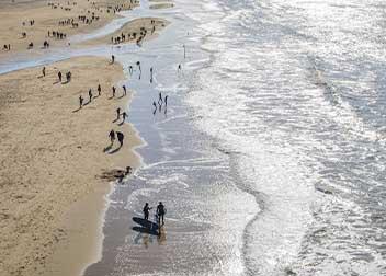 Mensen op het strand aan de kustlijn - Vriendenprijsreizen