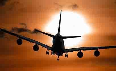 Vliegtuig in de lucht met ondergaande zon - Blog vakantie doorverkopen