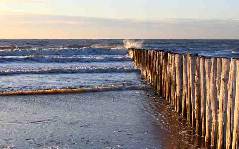 Golven in de zee die tegen een houten golfbreker aan slaan - goedkoop vakantie