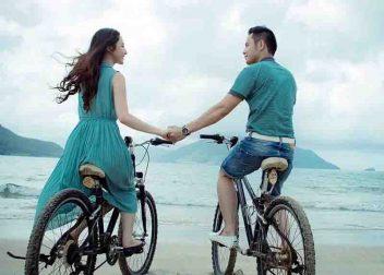Jong stel met hun fiets op het strand - vakantie bieden Vriendenprijsreizen