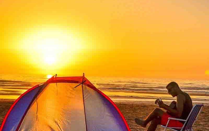 Man zit gitaar te spelen op het strand met op de achtergrond de ondergaande zon - Vriendenprijsreizen last minute