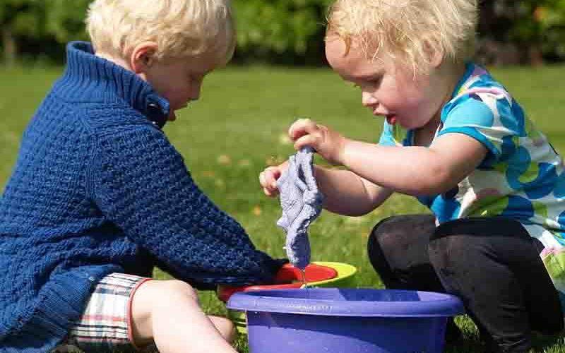 Spelende kinderen met water en een afwasteiltje op de camping - last minute vriendenprijsreizen