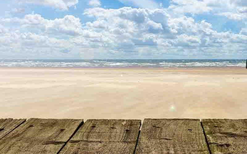 Strand met op de achtergrond de zee en sluimerwolken - goedkoop vakantie