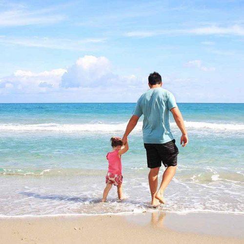 Vader en dochter lopen door de zee aan de vloedlijn - vakantie verkopen bij Vriendenprijsreizen