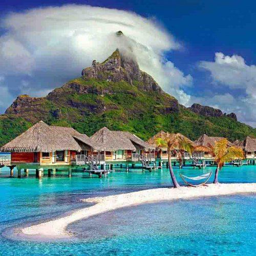 Vakantiebungalows in de zee op het bora bora eiland met op de achtergrond de berg - vakantie verkopen bij Vriendenprijsreizen