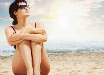 Vrouw op het strand met de zee op de achtergrond - aanbiedingen bij Vriendenprijsreizen