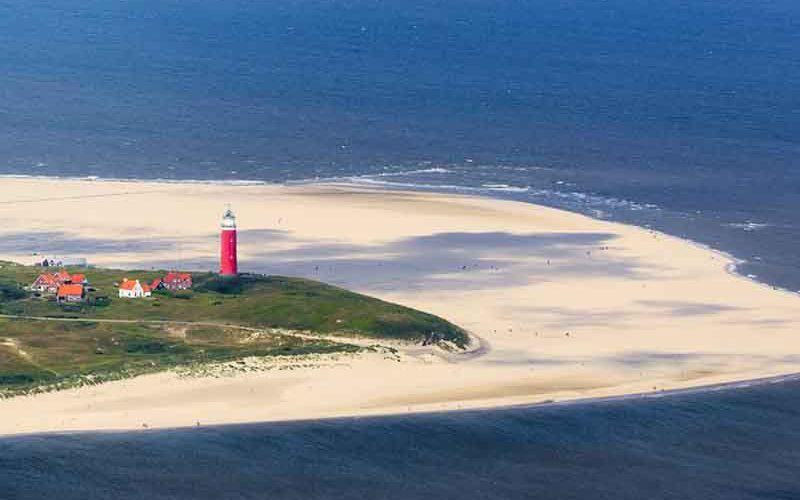 Vuurtoren in texel vanuit de lucht een foto genomen met op de achtergrond de zee - goedkoop vakantie